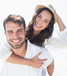 couple wearing white smiling on the beach