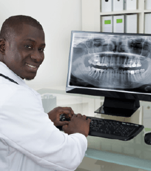 Dentist looking at digital x-rays on computer