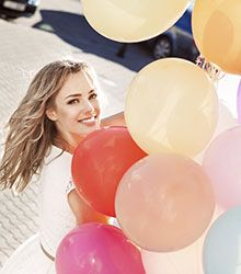 Brampton Cosmetic Dentistry Blonde hair woman holding pink balloons