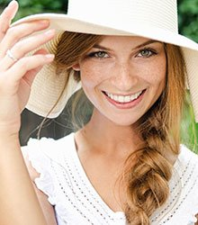 Beautiful woman wearing a white hat and a smile