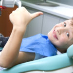 Young boy in a dental chair giving thumbs up
