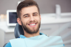 young man smiling sitting in chair after dental visit