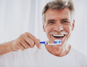 older man brushing his teeth to prevent dental bridge failure
