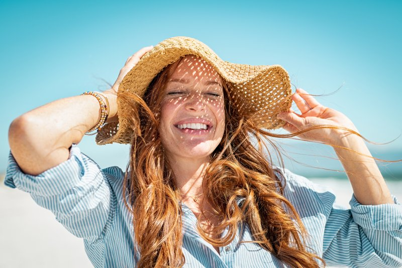 Woman in straw hat smiling on a beach
